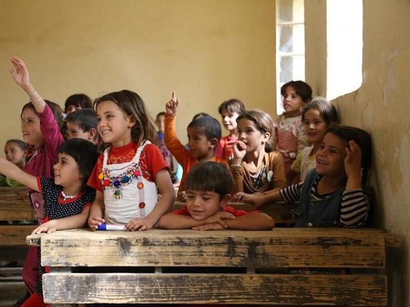 Iraqi children raising their hands in a classroom