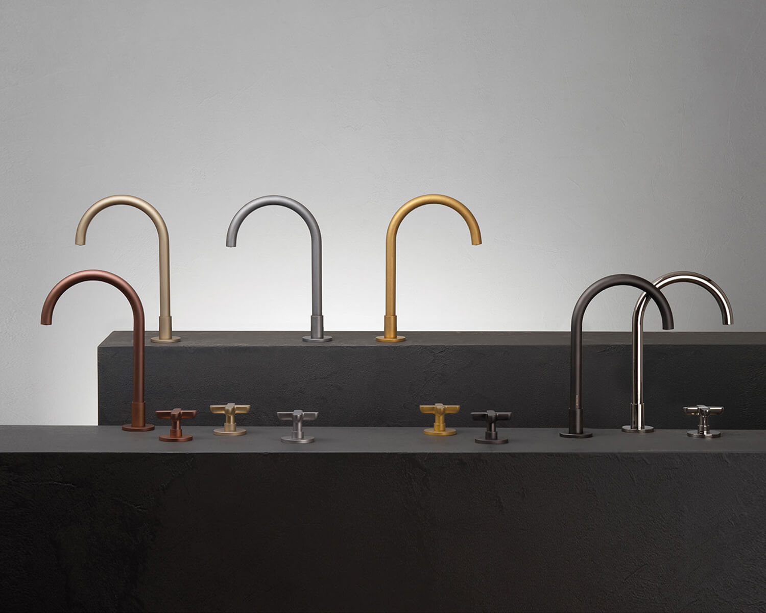 Icona Classic Collection in various PVD finishes: Matte Copper, Matte British Gold, Raw Metal, Pure Brass, Matte Gun Metal & Polished Nickel, arranged on 2 grey stone plinths of different heights