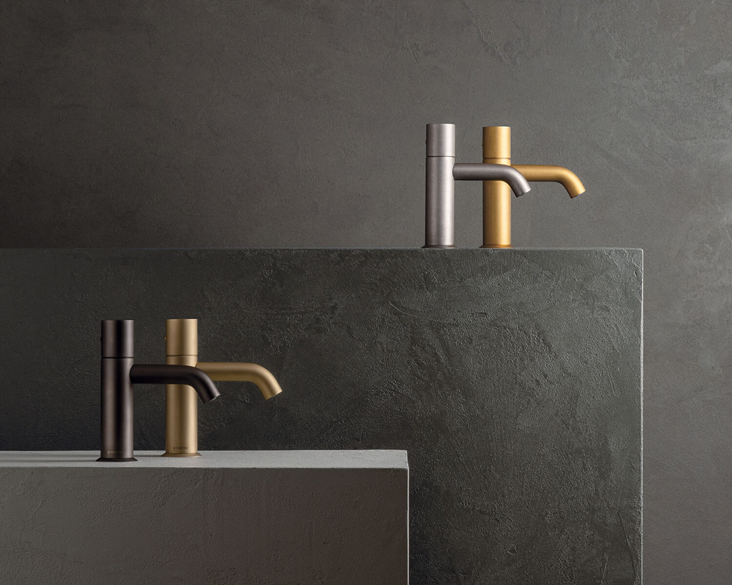 The Nostromo Collection in various PVD finishes: Matte Gun Metal, Matte British Gold, Raw Metal, Pure Brass, arranged on 2 grey stone plinths