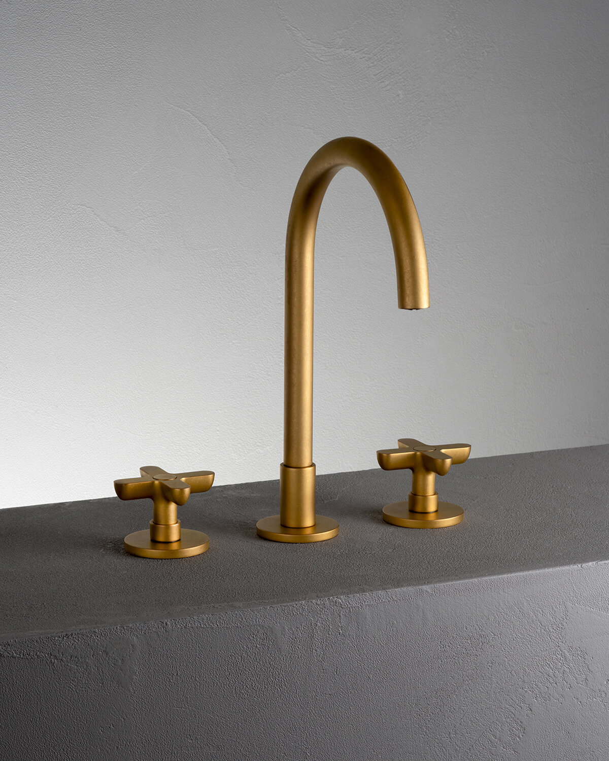 Icona Classic, Three-Hole Faucet, Pure Brass, on a grey stone plinth in front of a grey wall