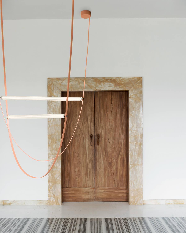 Pink Wireline light hung in front of a wooden door