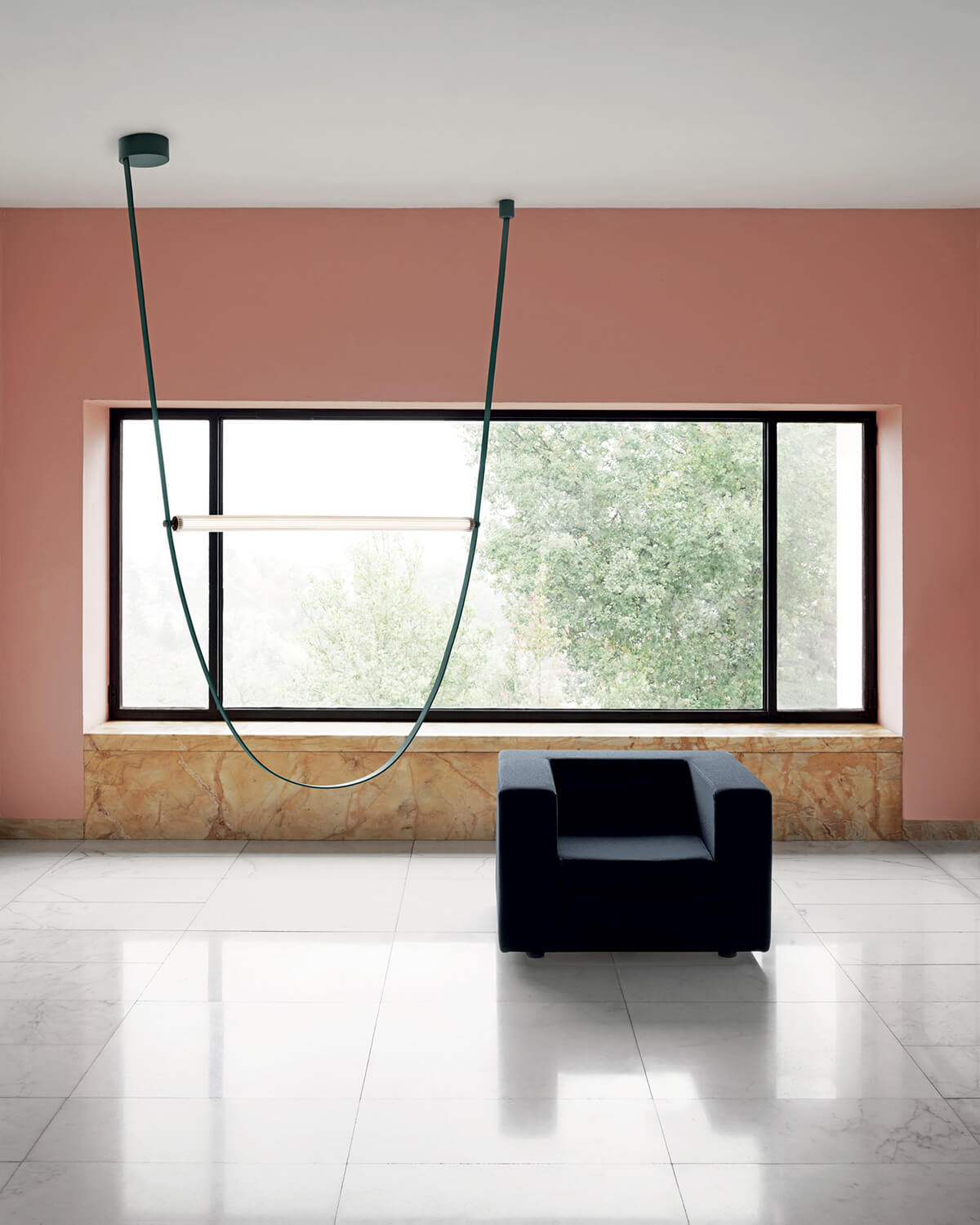 Green Wireline light hung in front of a pink wall, next to a black armchair