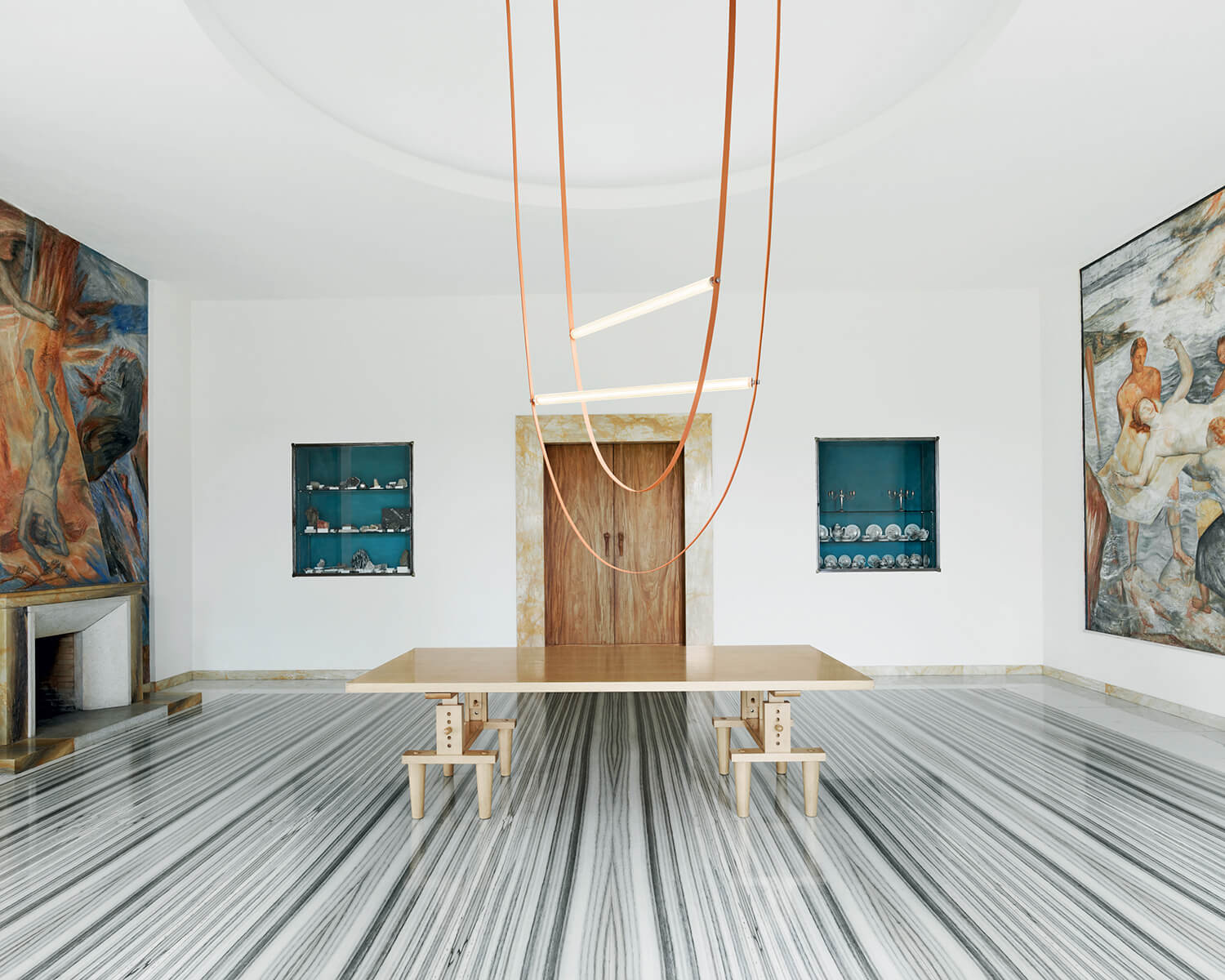 Pink Wireline light hung in the centre of a gallery over a light-coloured wood table