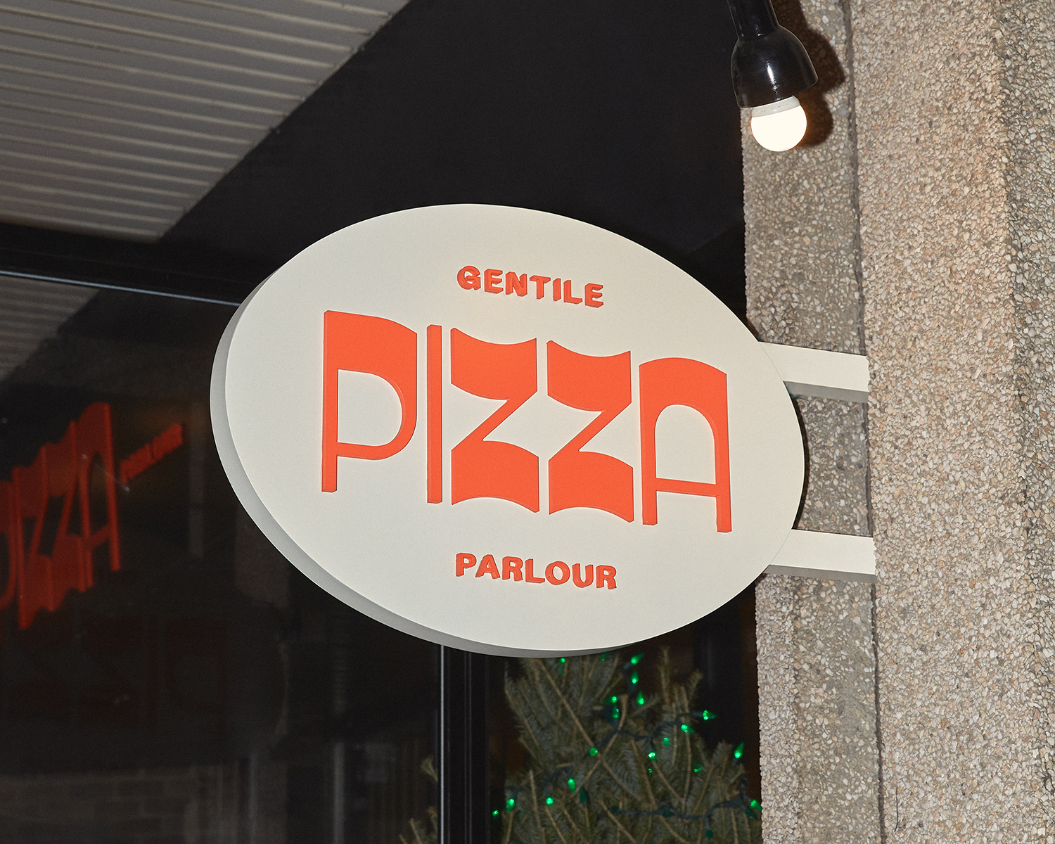 Gentile Pizza Parlour in orange text on white oval sign