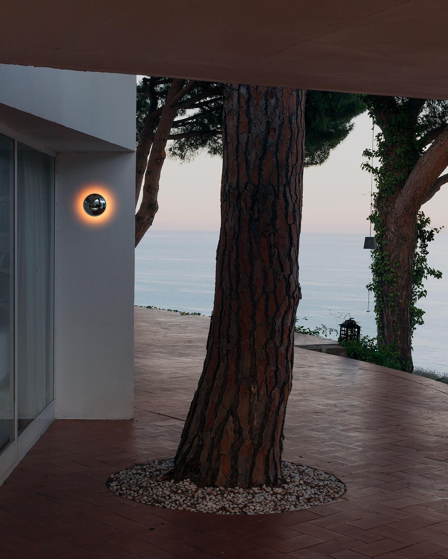 Babila Sconce mounted on a wall next to a tree