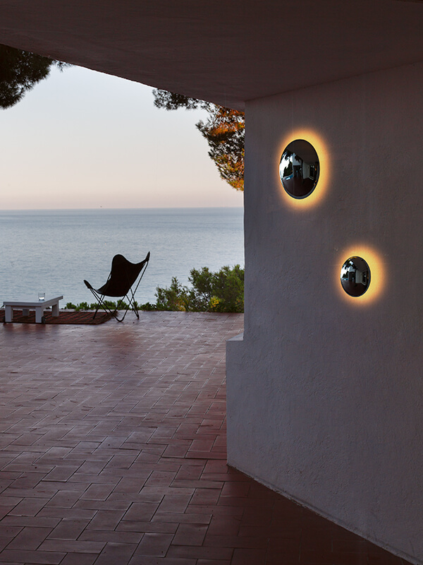 Small and large Babila Sconces mounted on a wall next to a brick patio overlooking the water