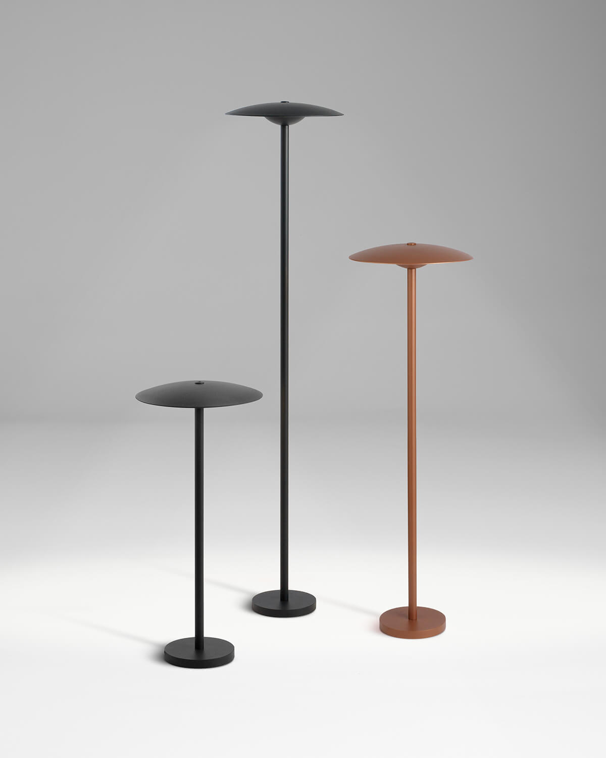 Large black, medium brown, and small black Ginger Bollard lamps arranged in a cluster on plain grey background