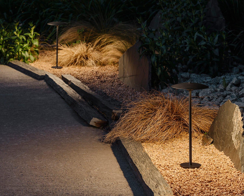 Two Bollard lamps lighting a gravel path at night