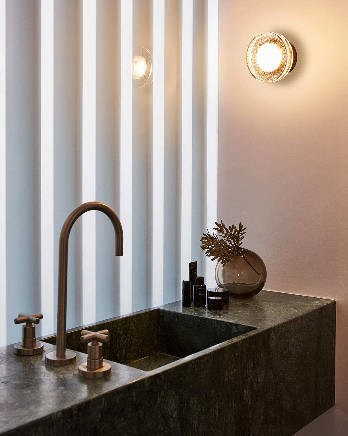 Roc Sconce mounted next to a marble bathroom sink