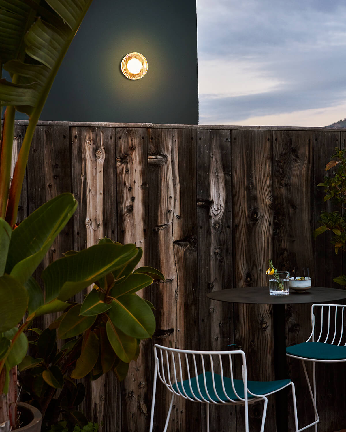 Roc Sconce mounted on a teal wall behind a wooden fence and bar-height seating area