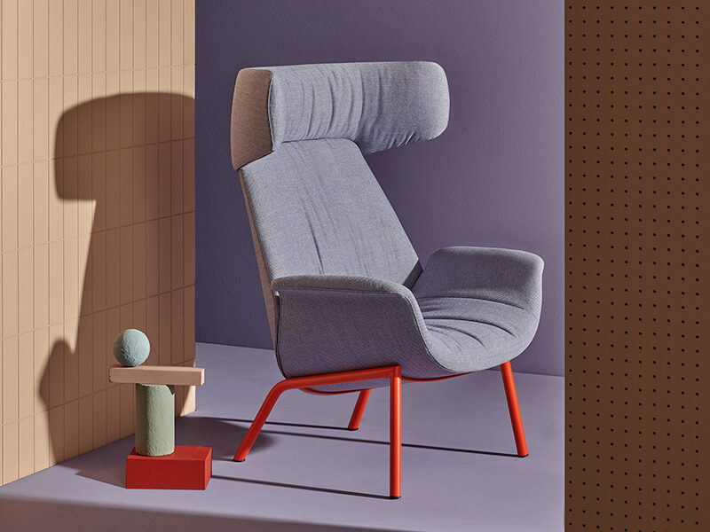 Purple Ila chair with headrest and red metal legs in front of purple and peach walls, next to a side table