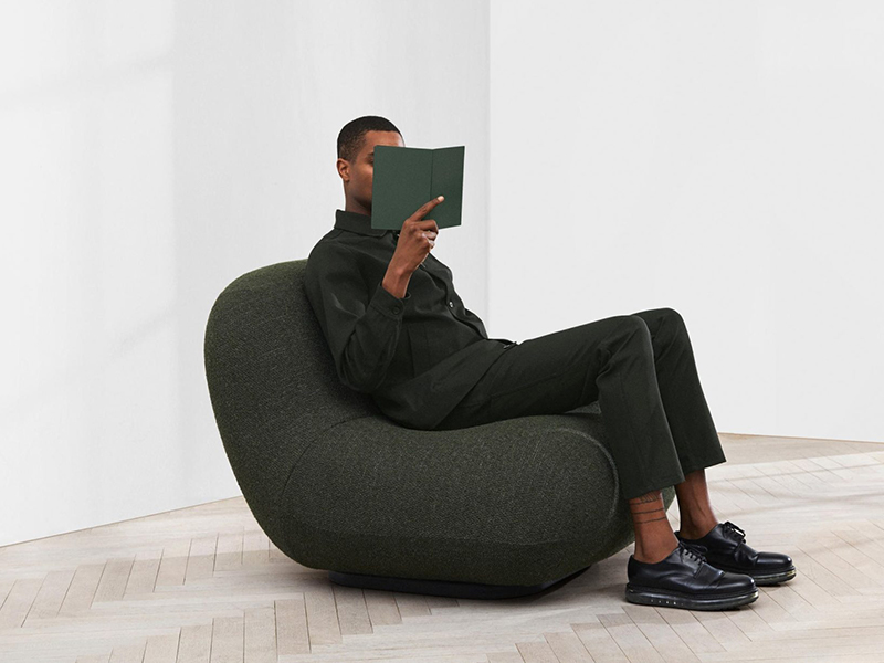 Man sitting in grey chair reading a book