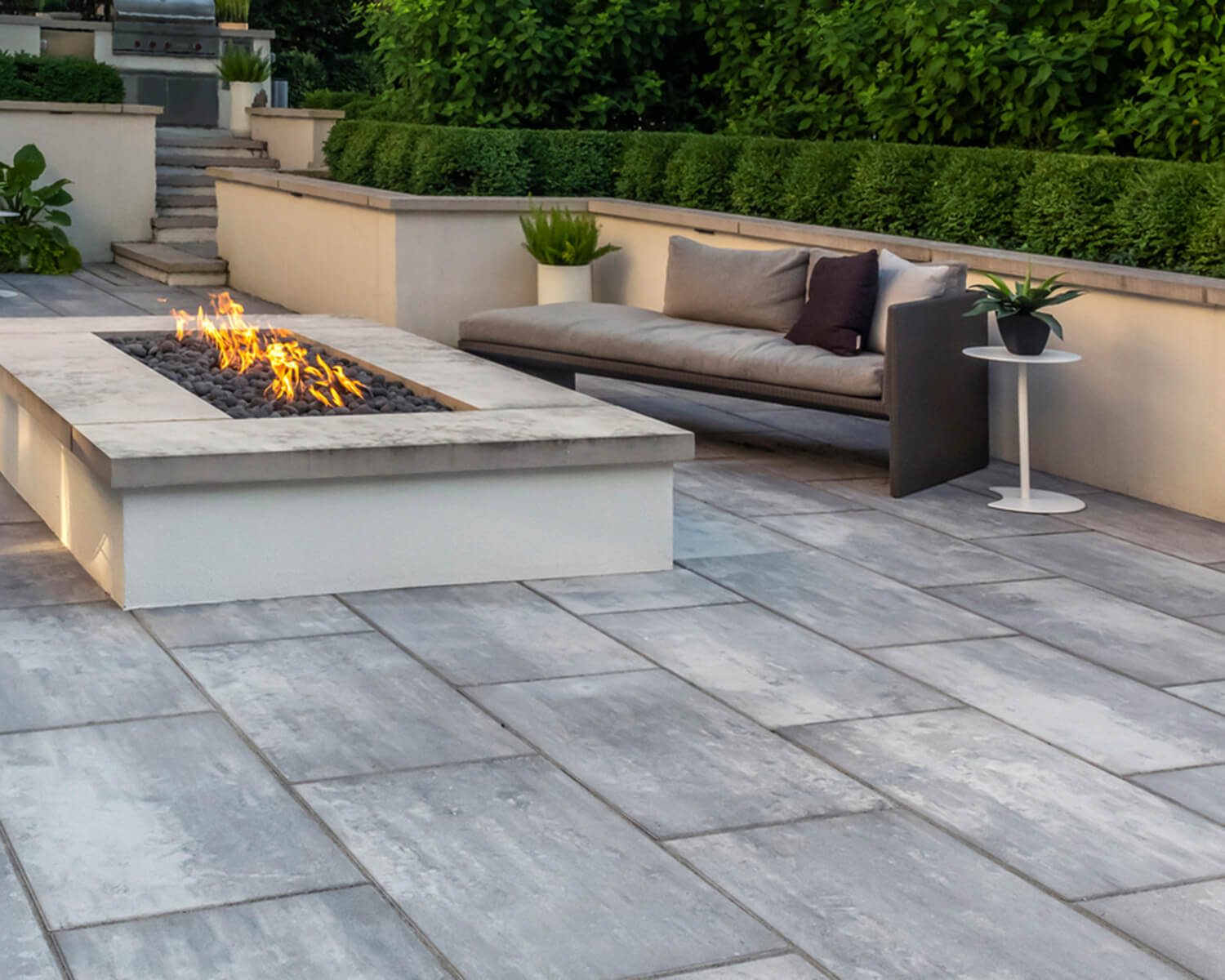 Grey Unilock slabs on a deck, with an outdoor fireplace and sofa