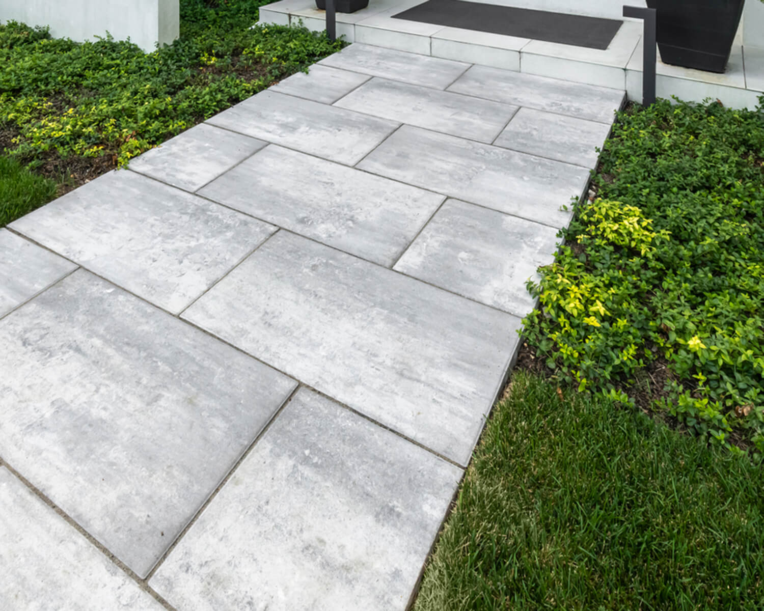 Light grey Unilock slab path surrounded by grass