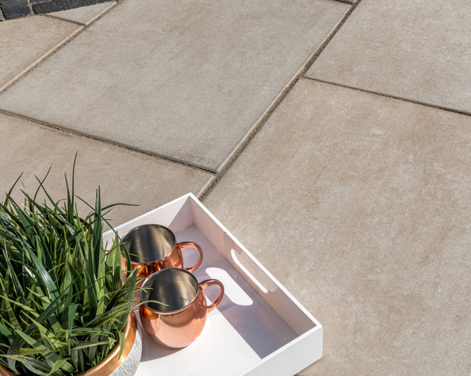 Close-up view of Unilock slab, with tray holding a plant and 2 mugs