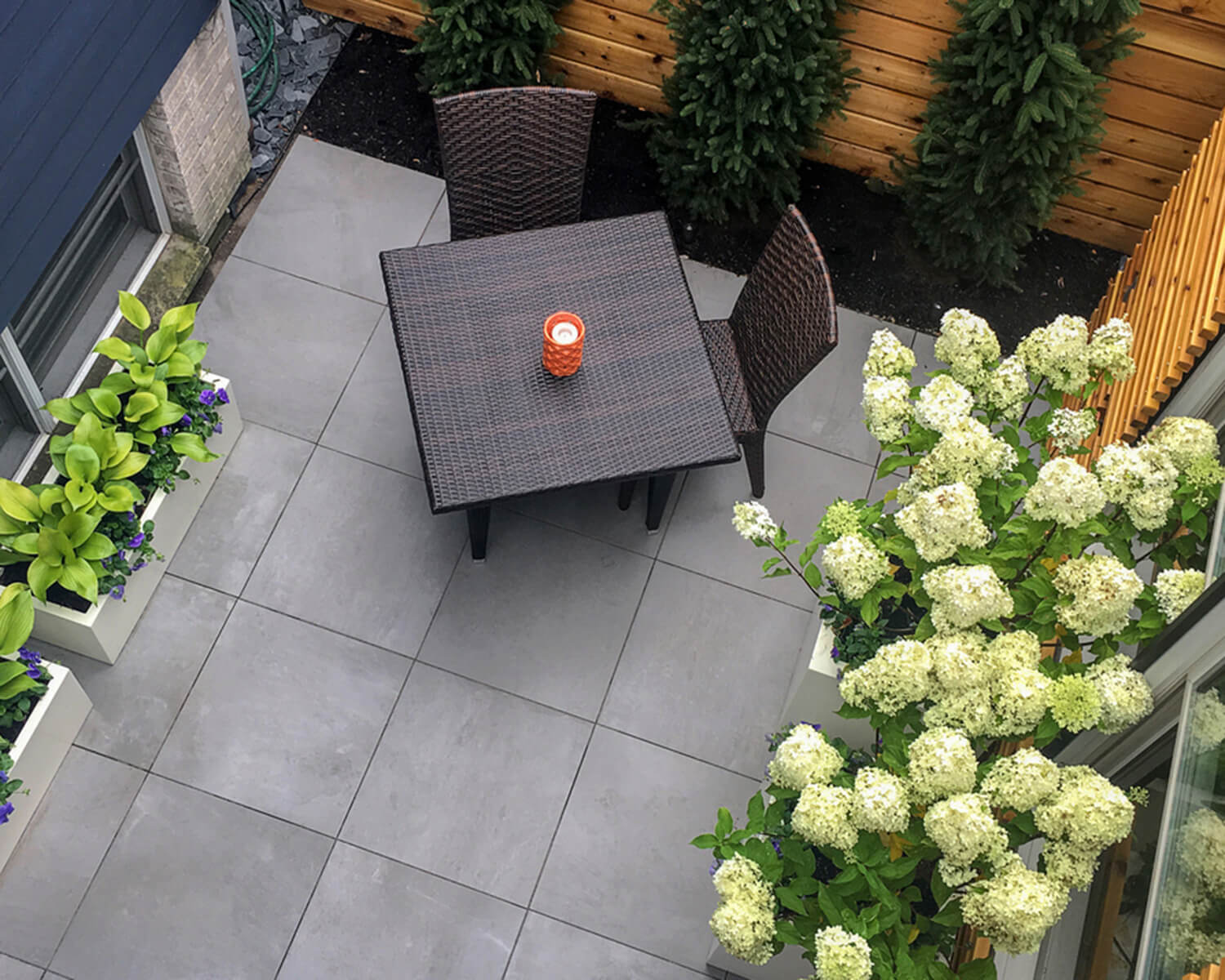 Grey Unilock slabs on a roof deck, which has 2 brown dining chairs and a table
