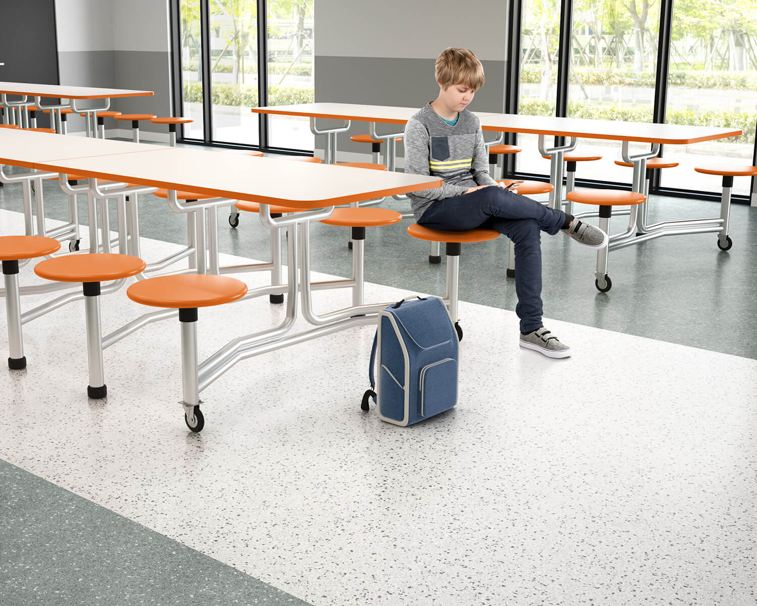Boy sitting at white table with orange seats