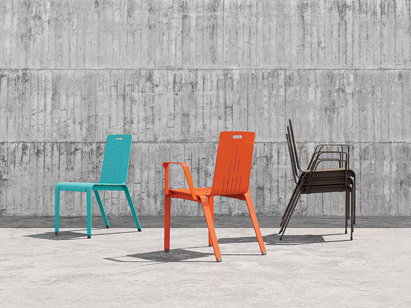 Aqua, orange, and brown ALUM chairs in front of a concrete wall