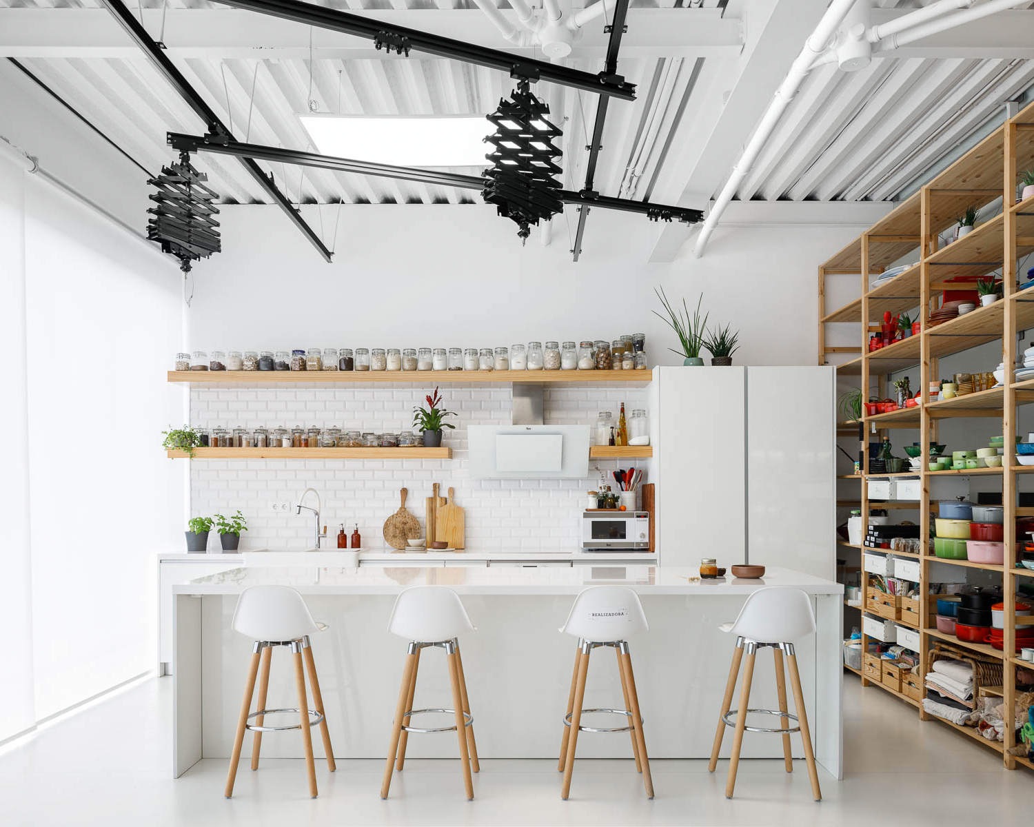 View of the kitchen with white counter stools, white cabinets, and wooden shelving housing colourful cookware
