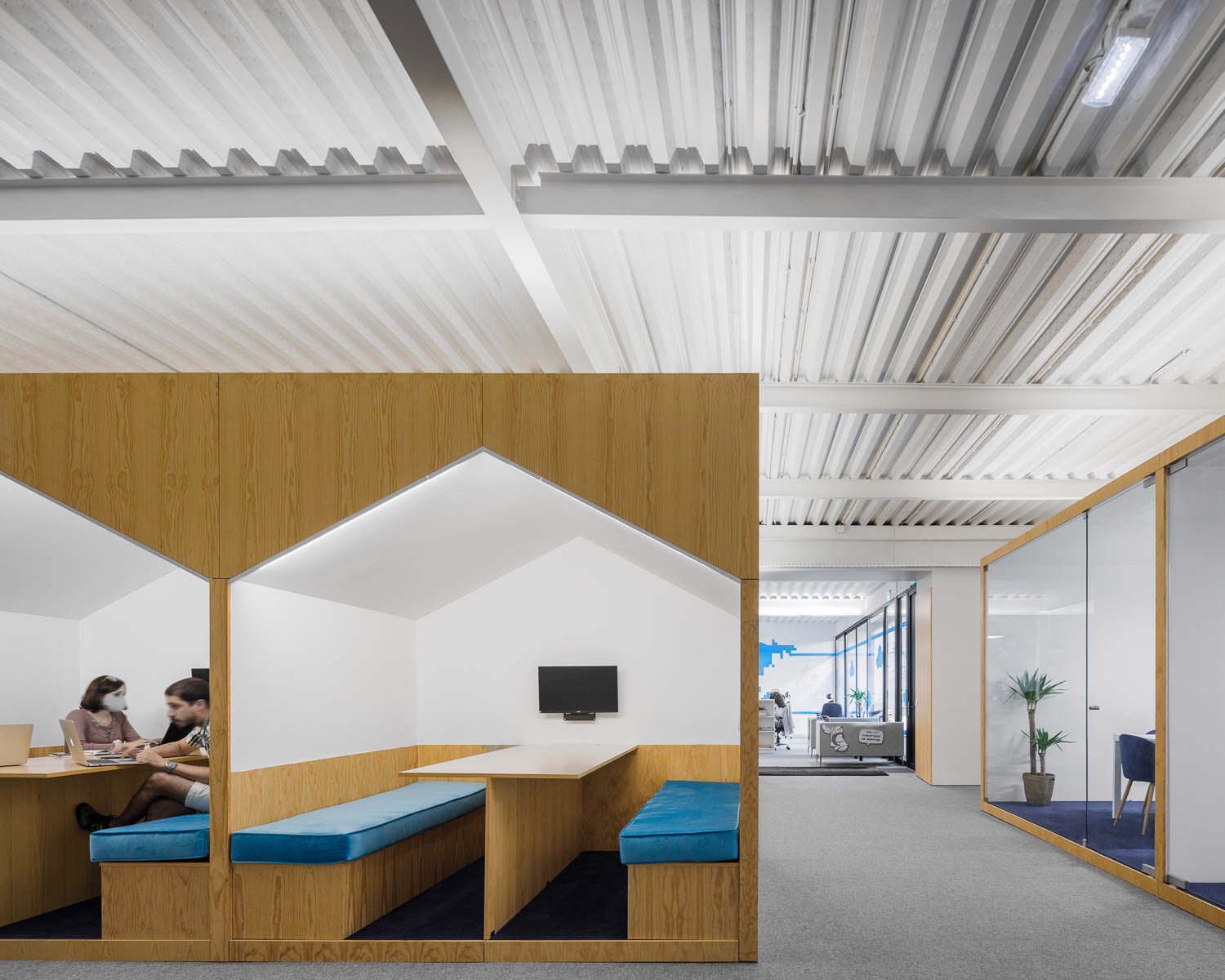 View of office showing wood-clad meeting booths with blue upholstered benches