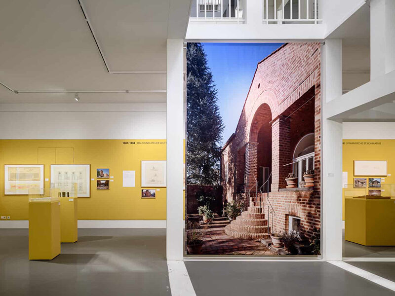 View inside exhibit showing large photo of a red brick building, yellow walls and pedestals