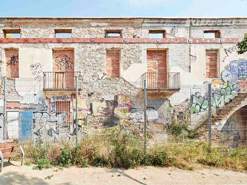 Building with graffiti and a fence in front