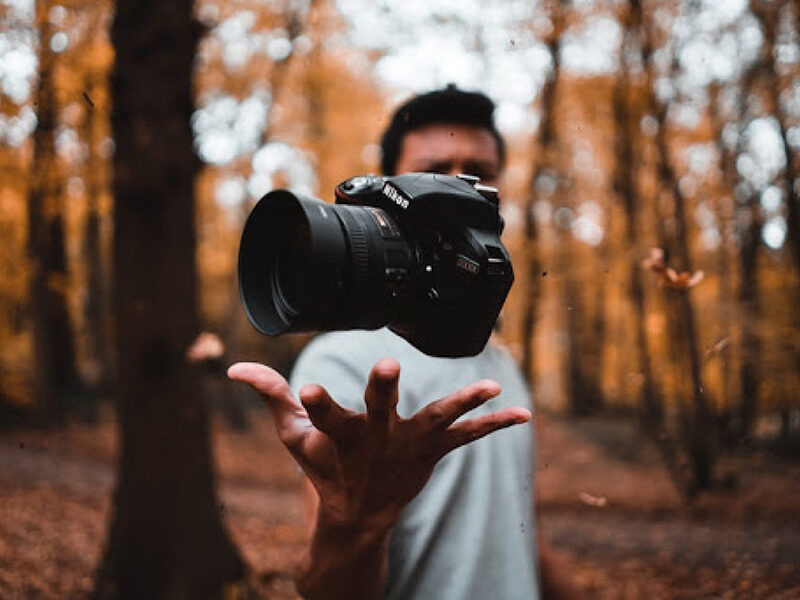 Man throwing camera up in the air in a forest
