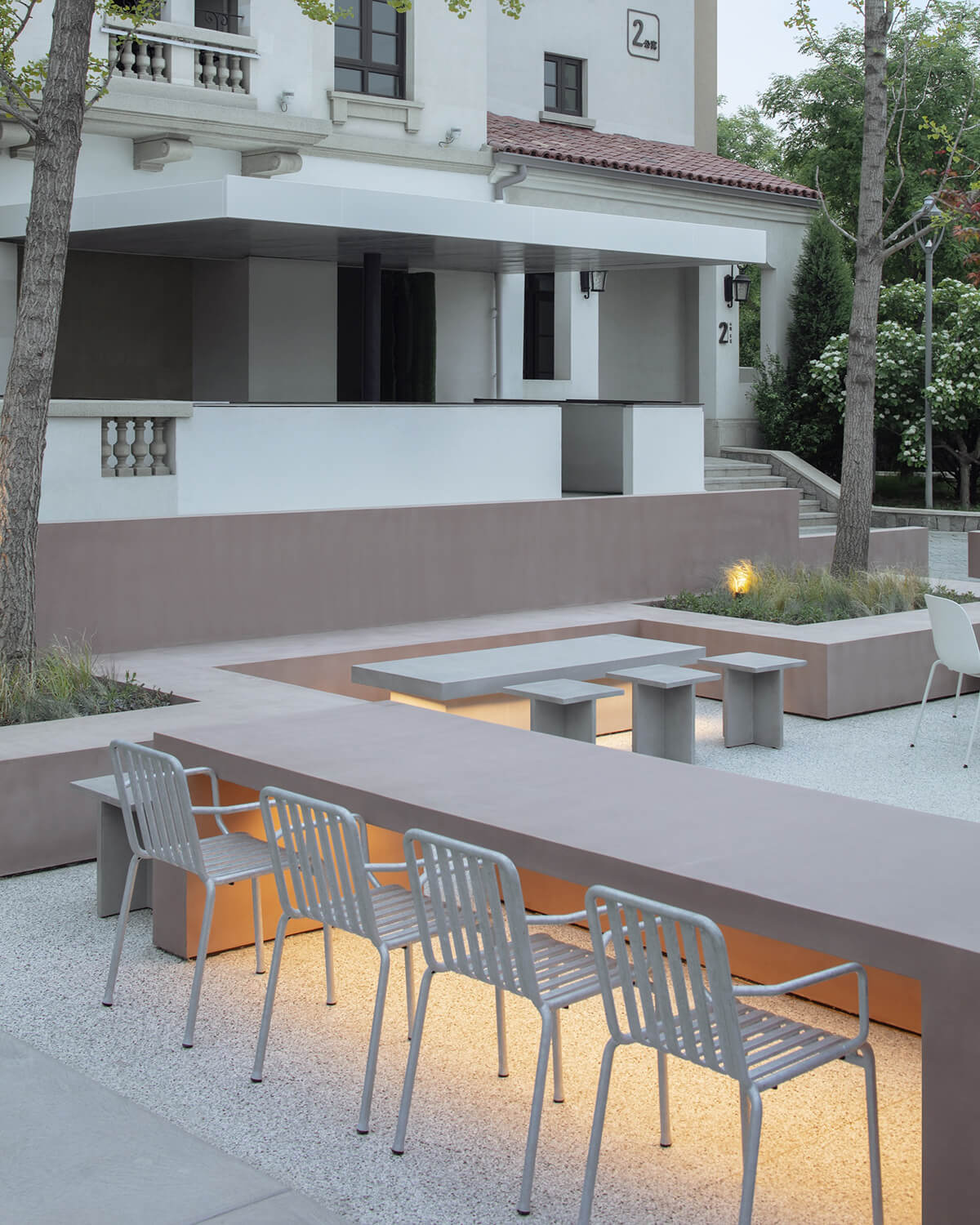 Close-up view of the outdoor seating area showing integrated Dagu cement tables and white chairs