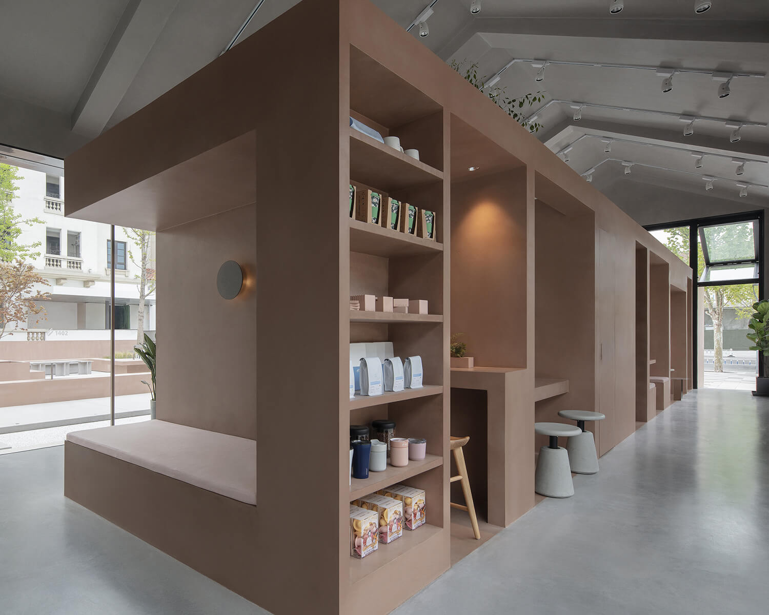 Interior view showing the new cement volume containing open shelving and seating space