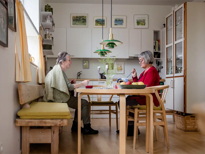Two senior women eating at a wooden dining table with green pendant lights overhead