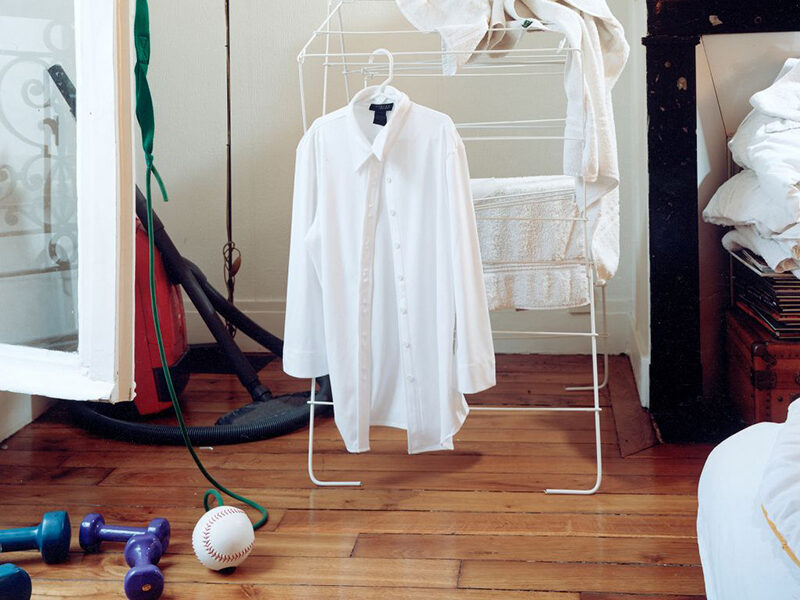 Room with a white shirt hanging, and weights and baseball on the floor