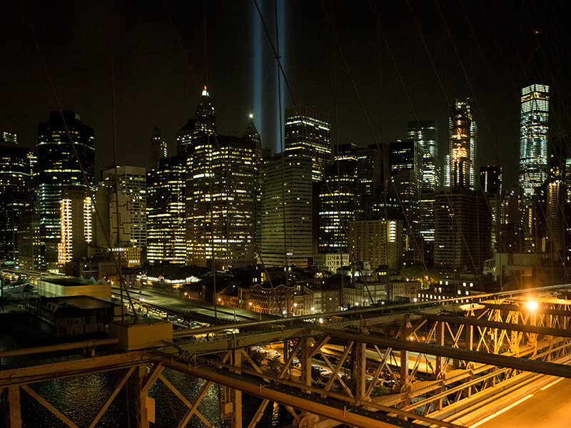 """View west from the Brooklyn Bridge capturing the annual September 11 """"Tribute in Light,"""" a commemorative art installation that recreates the shapes of the towers, Brooklyn, New York; 2017."""